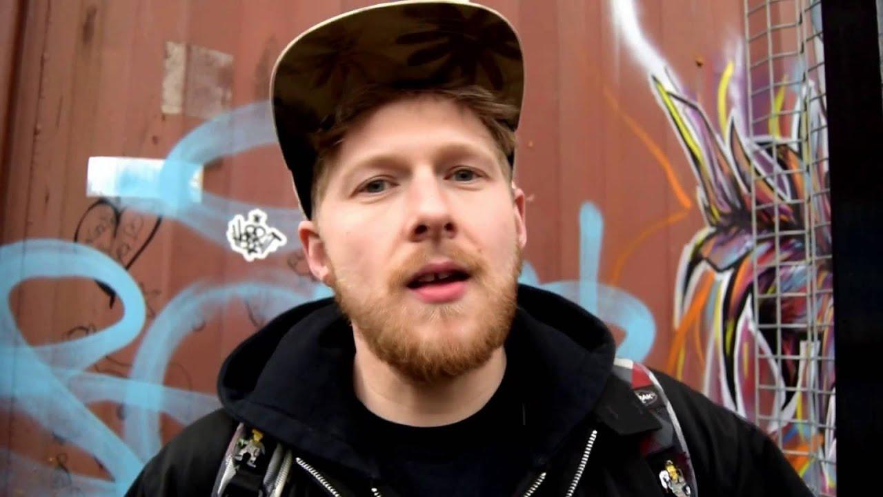 Artist wears cap in front of graffiti