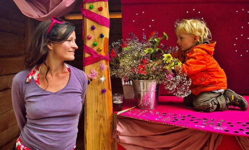 Lady and child look at each other, with flowers and ribbons around