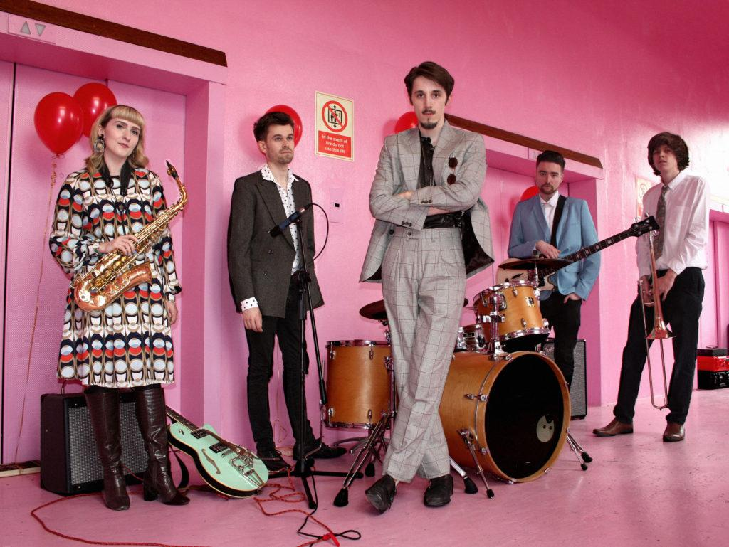 5-piece band in a pink room