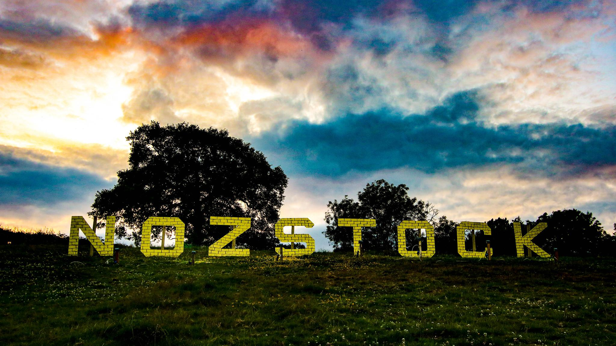 Yellow brick Nozstock sign against trees and sunset