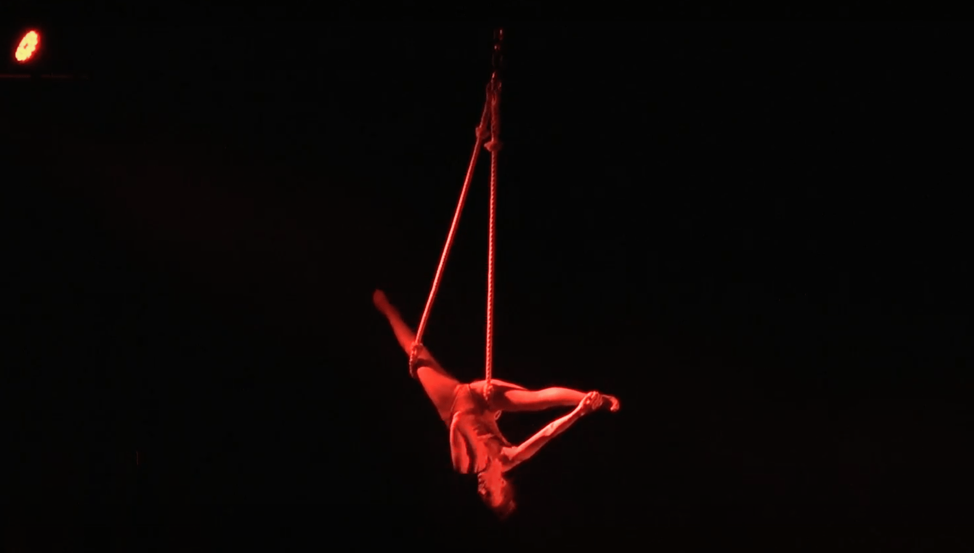 Nix hangs lit red from a trapeze