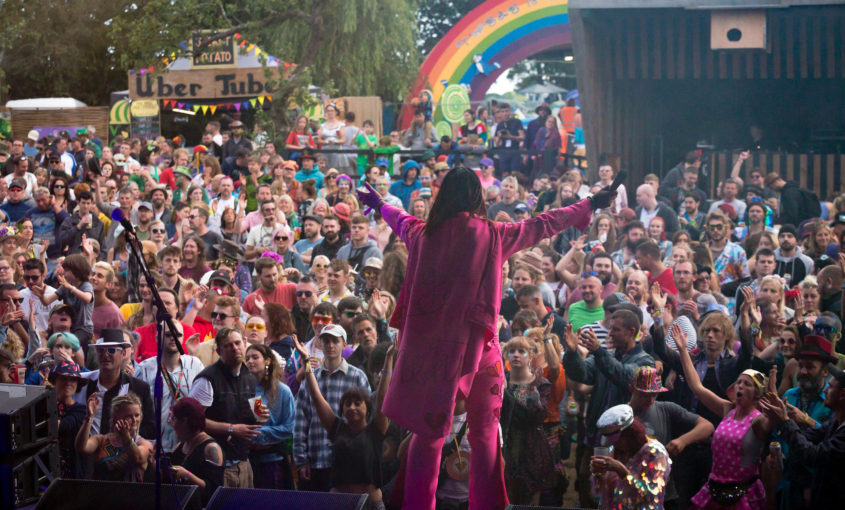 a man in pink cape arms outstretched towards a crowd of festival goers. A rainbow in the distance.