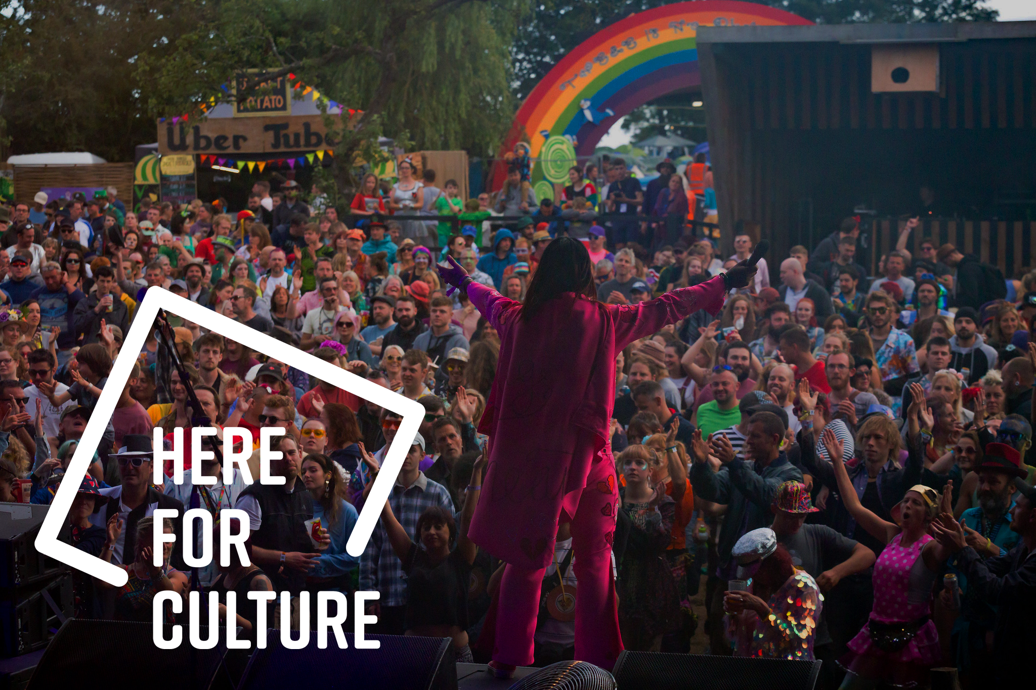 Here for Culture logo with a man in pink cape arms outstretched towards a crowd of festival goers. A rainbow in the distance.